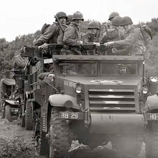 black and white image of american soldiers in trucks